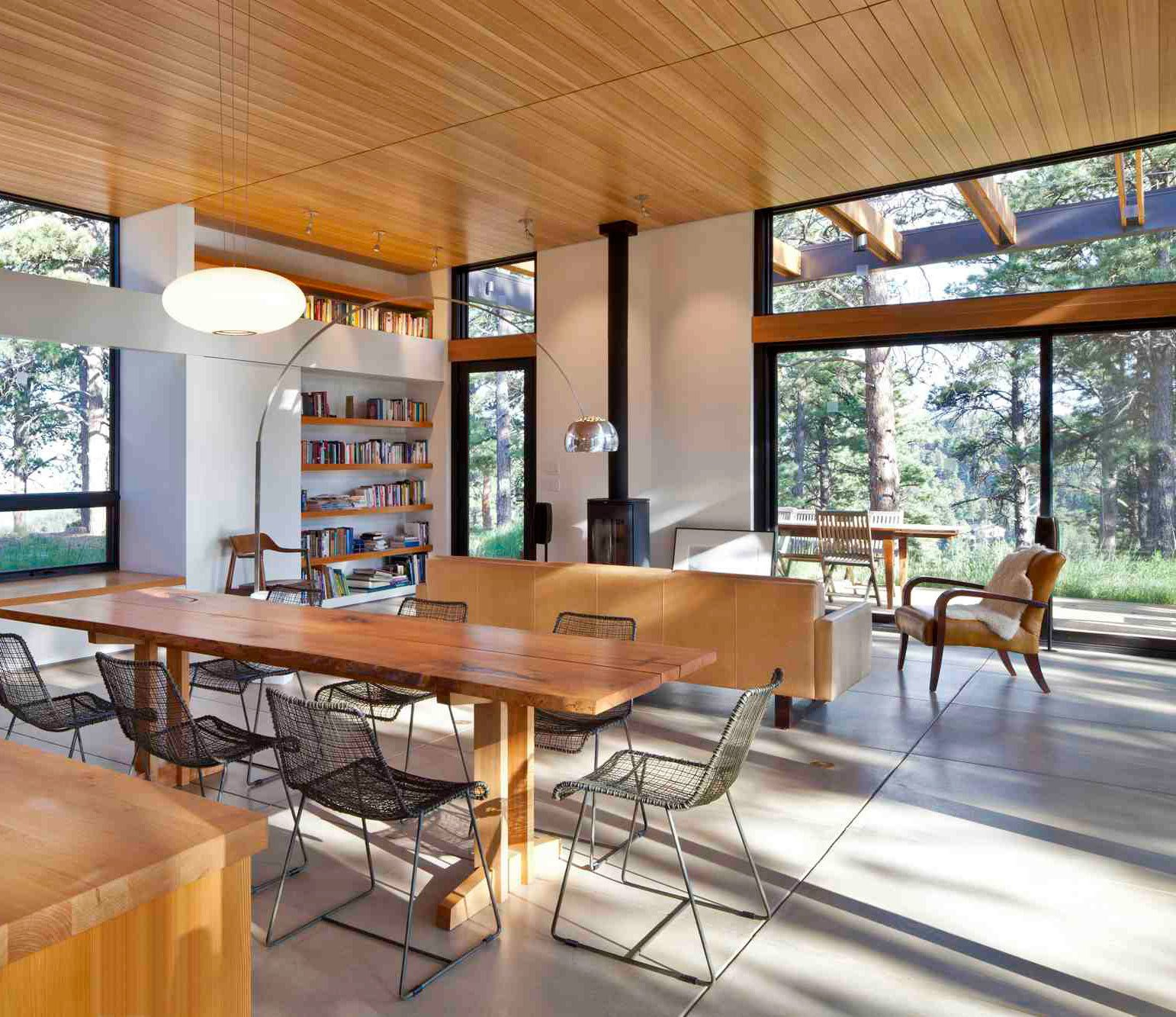 Tall, sliding glass panels extend along the west side of the house, including into the living area, which has views across the terrace and 35-acre wooded property. Built-in bookshelves, part of Dynia's thick-wall strategy, keep with the orderly design.   Photo by Ron Johnson.