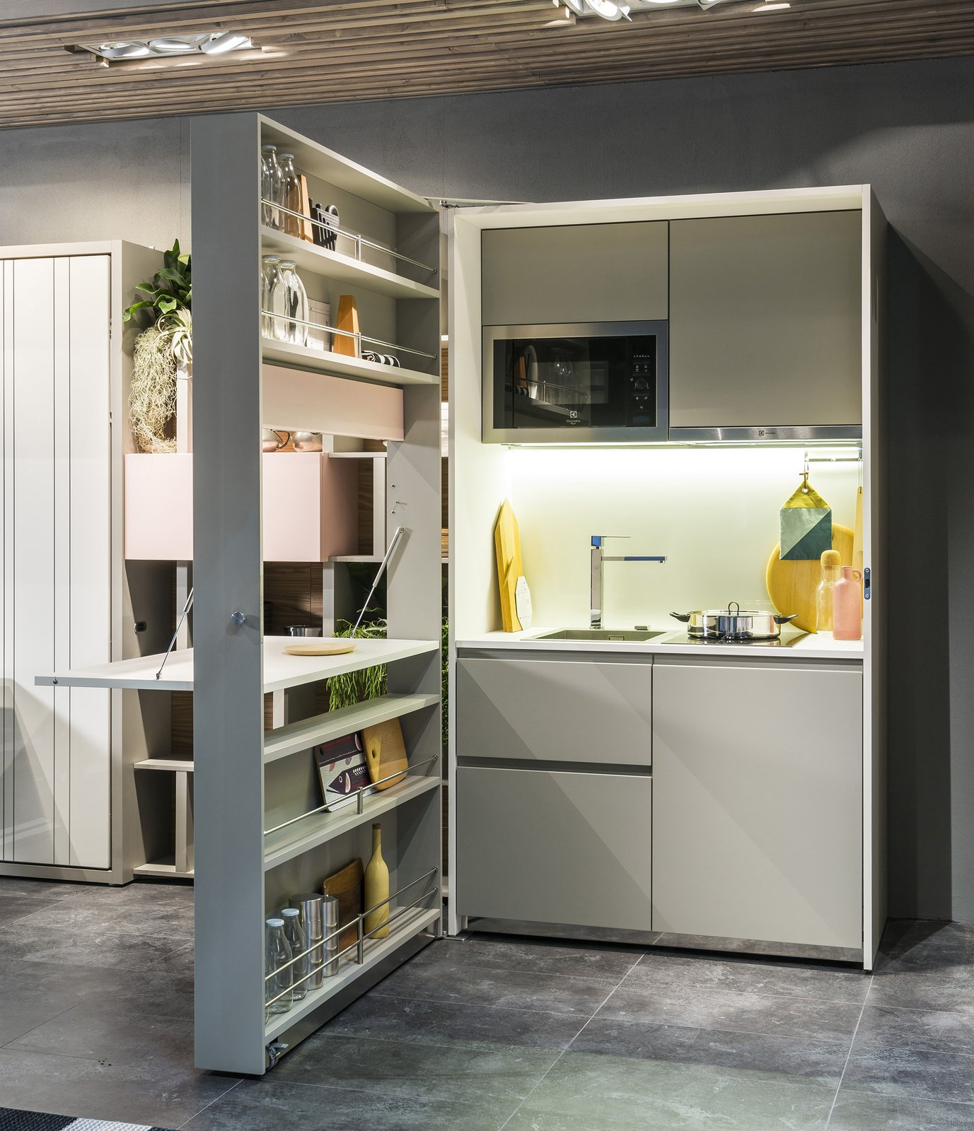 The Box Kitchen contains two burners, a ventilation hood, a sink, a dishwasher, and a microwave. A fold-down laminated countertop creates a prep surface.  Solutions For Tiny Kitchens by Aileen Kwun from Genius Unfolding Kitchen Tucks Neatly Into Small Spaces