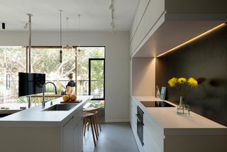 10 Best Dwell Studios and Modern Apartments - Photo 8 of 10 - In the kitchen, the custom cabinets contain special compartments that hide appliances from sight. The room draws in natural light from the balcony.