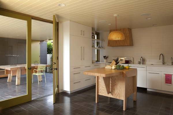 The kitchen island was also a custom design by Clementi and Smith-Clementi. The pendant light overhead is a BÖJA from Ikea reconfigured by the architects. The floor tiles are made of concrete and are from Granada Tile.