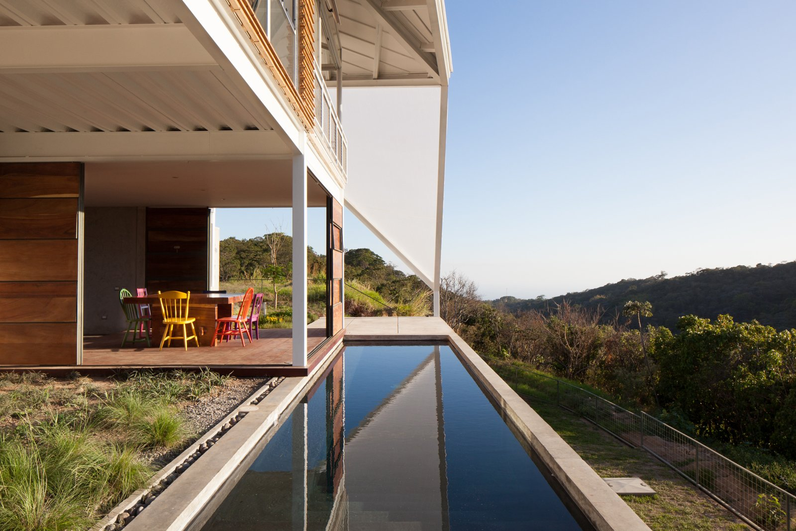 The back patio overlooks a swath of forest. Striking Green House with a View in El Salvador - Photo 4 of 7