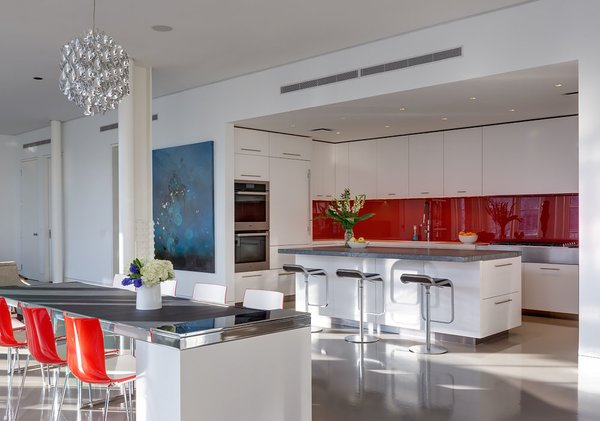 Though the home's common areas are largely white and monotone, the kitchen introduces a pop of red, the owner's favorite color, through the glossy AGC kitchen backsplash. Stone pietra cardosa counters are used on the center island, along with white Corian around the perimeter. A Miele range, Sub-Zero refrigerator, and Piston stools by Shin and Tomako Azumi complete the space.