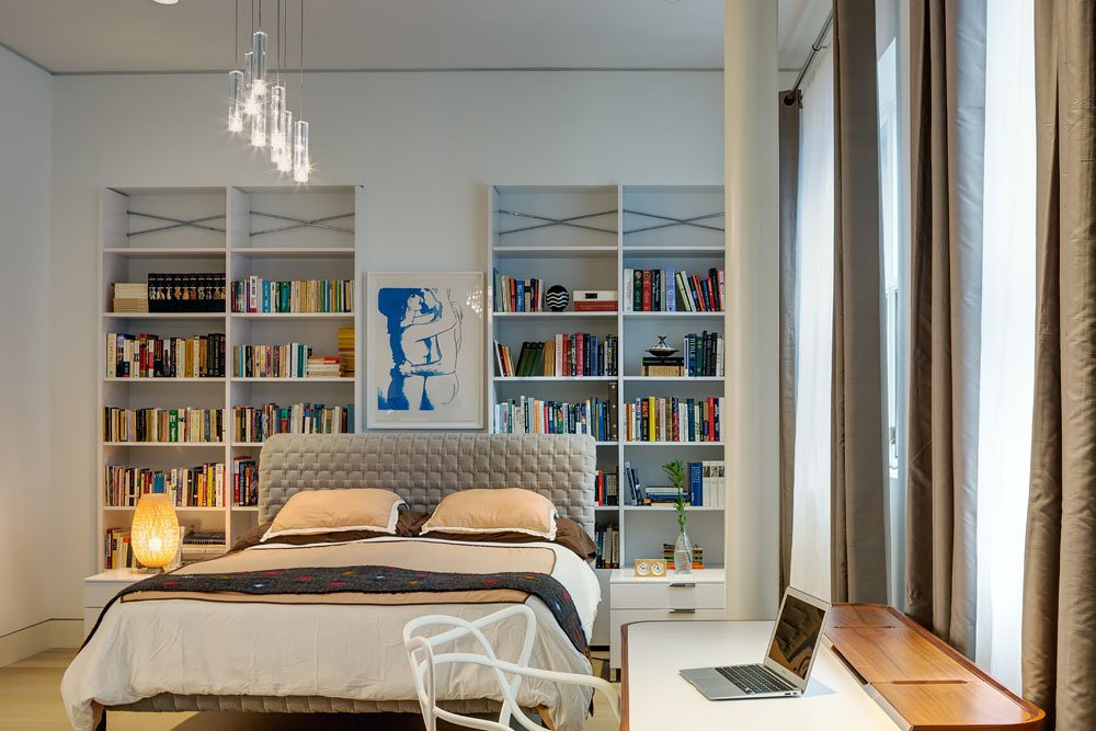 In the master bedroom, a small workstation is accented by a Philippe Stark desk chair, and repurposed white shelving offers generous display space. Ten foot ceilings and expansive windows add to the open and airy feel of the room.  Bedrooms by Dwell from A Bright Brooklyn Loft with an Envy-Inducing Walk-In Closet