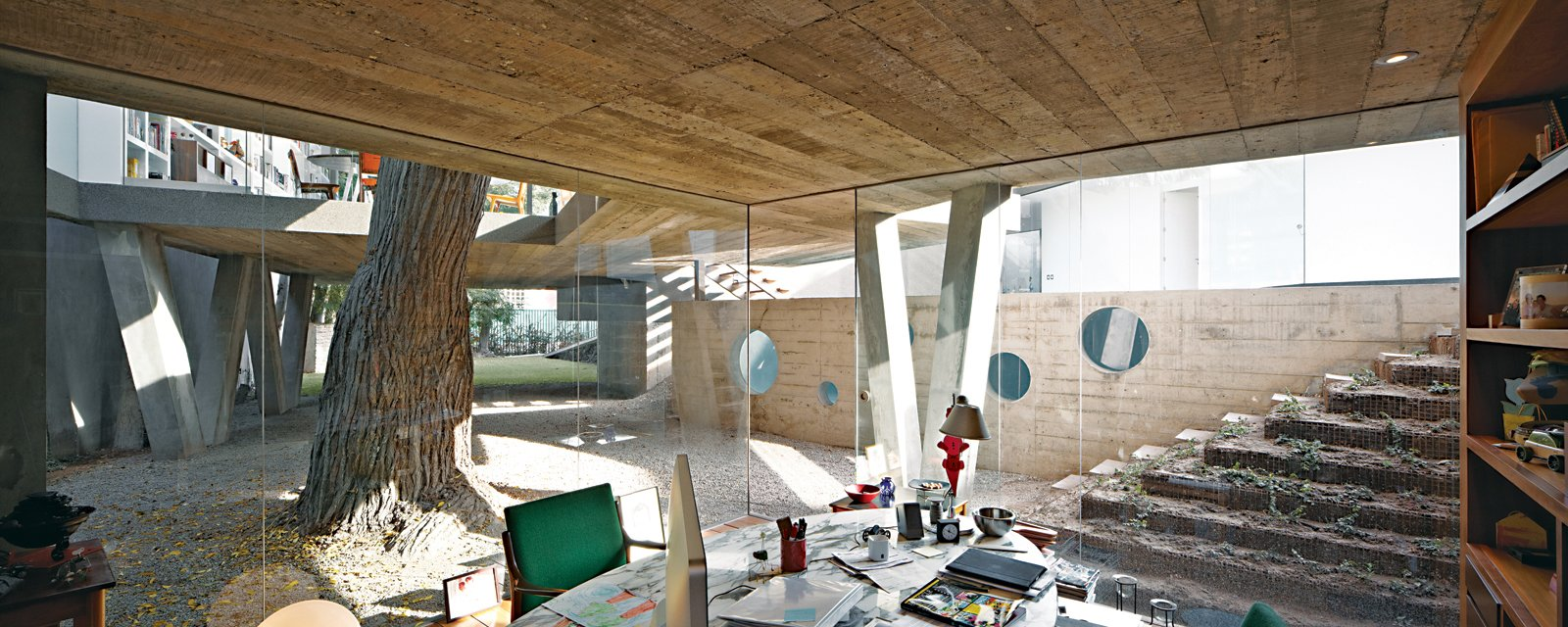 For a family in Lima, a team from local firm 51-1 Arquitectos built Casa Serpiente, which meanders around 25 existing trees. Husband Irzio's study is among the few ground-level rooms in the 4,300-square-foot house. A Modern Concrete Home in Peru - Photo 2 of 13