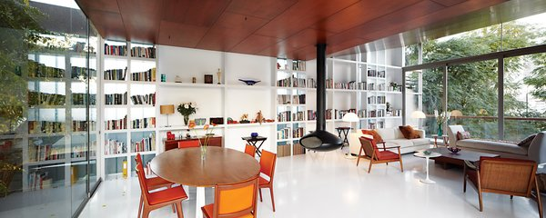A structural steel wall in the living area doubles as a built-in bookcase. The side chairs, floor lamps, and dining chairs were salvaged from the Hotel Crillón in Lima. The daybed and coffee table were designed by Maria Eugenia Alvarez-Calderón, who helped Irzio and Lisette with the interiors. The fireplace is from Fireorb and, as throughout, the floor is poured white acrylic by Química Suiza.