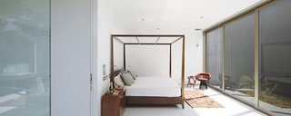 In the master bedroom is a four-poster bed by Javier Rubio and a vintage Warren Platner chair.