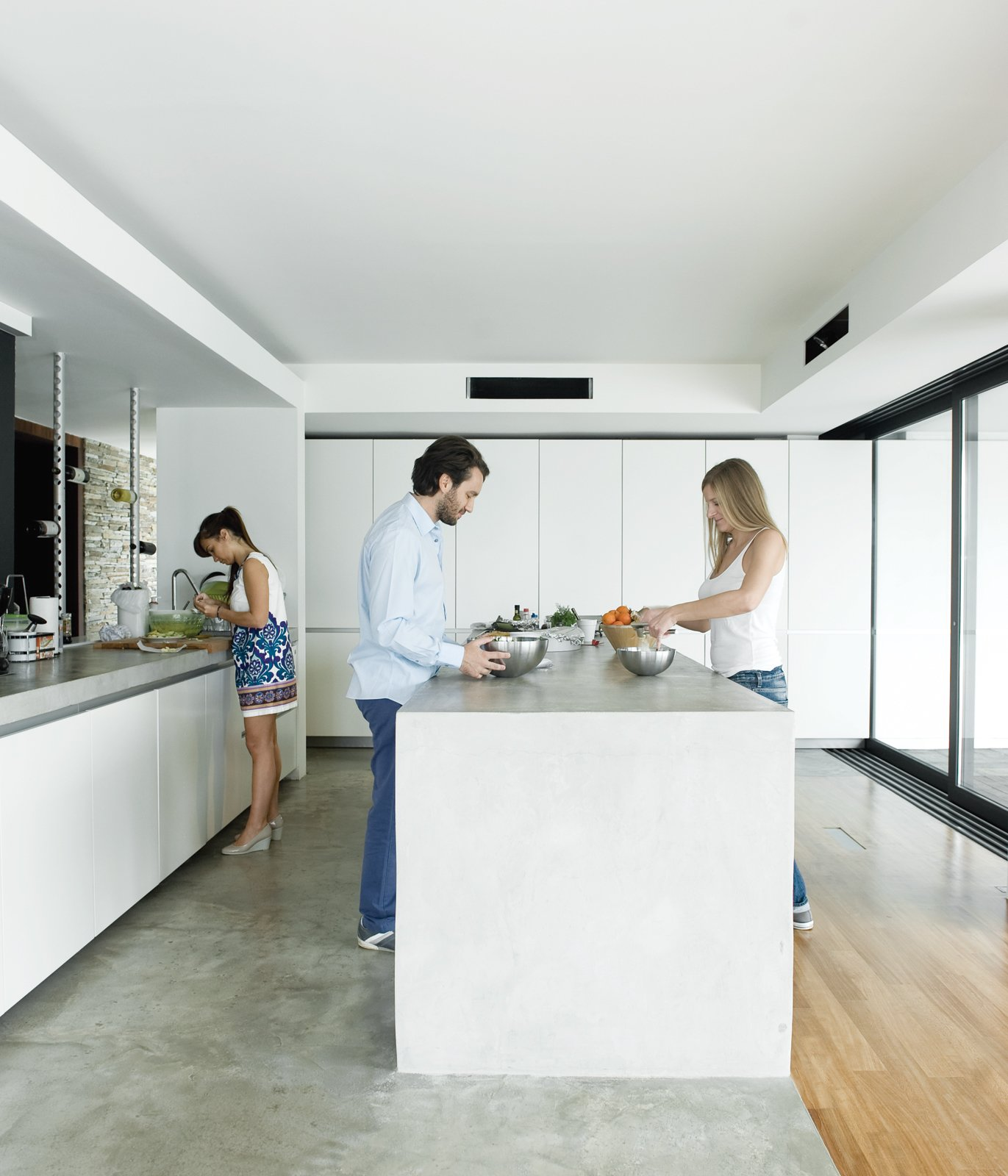 Alexia, Achilleas, and friend Fotini prepare lunch in the kitchen, outfitted with cabinets by Zeyko. Tagged: Kitchen, Concrete Counter, White Cabinet, Concrete Floor, and Light Hardwood Floor.  Photo 6 of 13 in An Idyllic Vacation Home in Greece