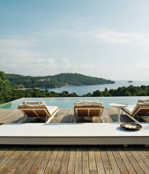 Made from white aluminum and oiled teak, the wooden sun loungers are from Viteo's Pure collection. The long low table is made of Corian by DuPont and comes from the same line of outdoor furniture.