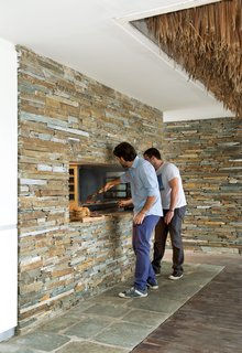 Achilleas and his friend Jovi tend the grill, which was Achilleas's own design and is supported by a concrete beam—cast with slate stones embedded in it—just above the opening.
