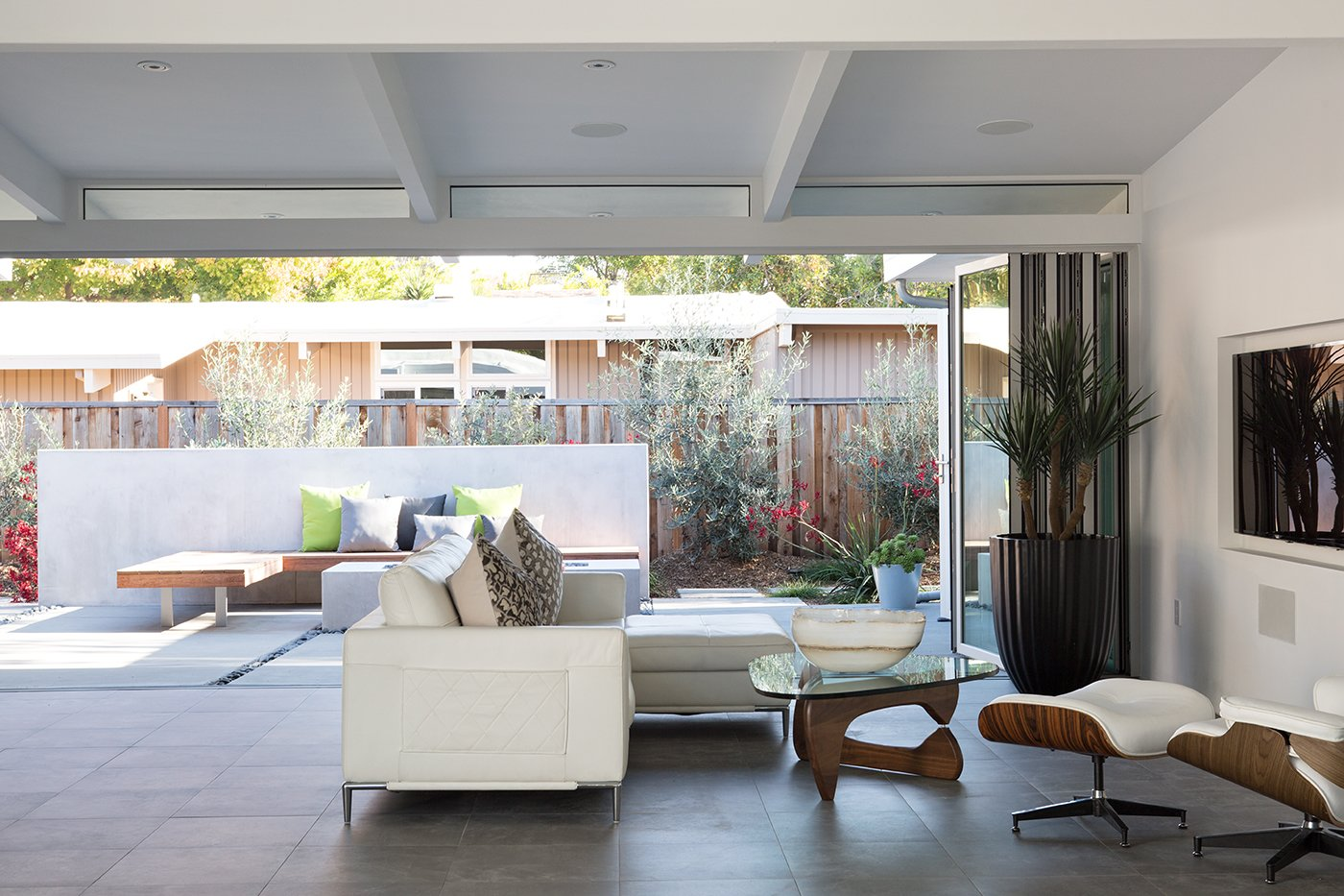 The home's sloping roofline guides the eye towards the outdoor living area. In the living room, occupants can relax in the Eames lounge.