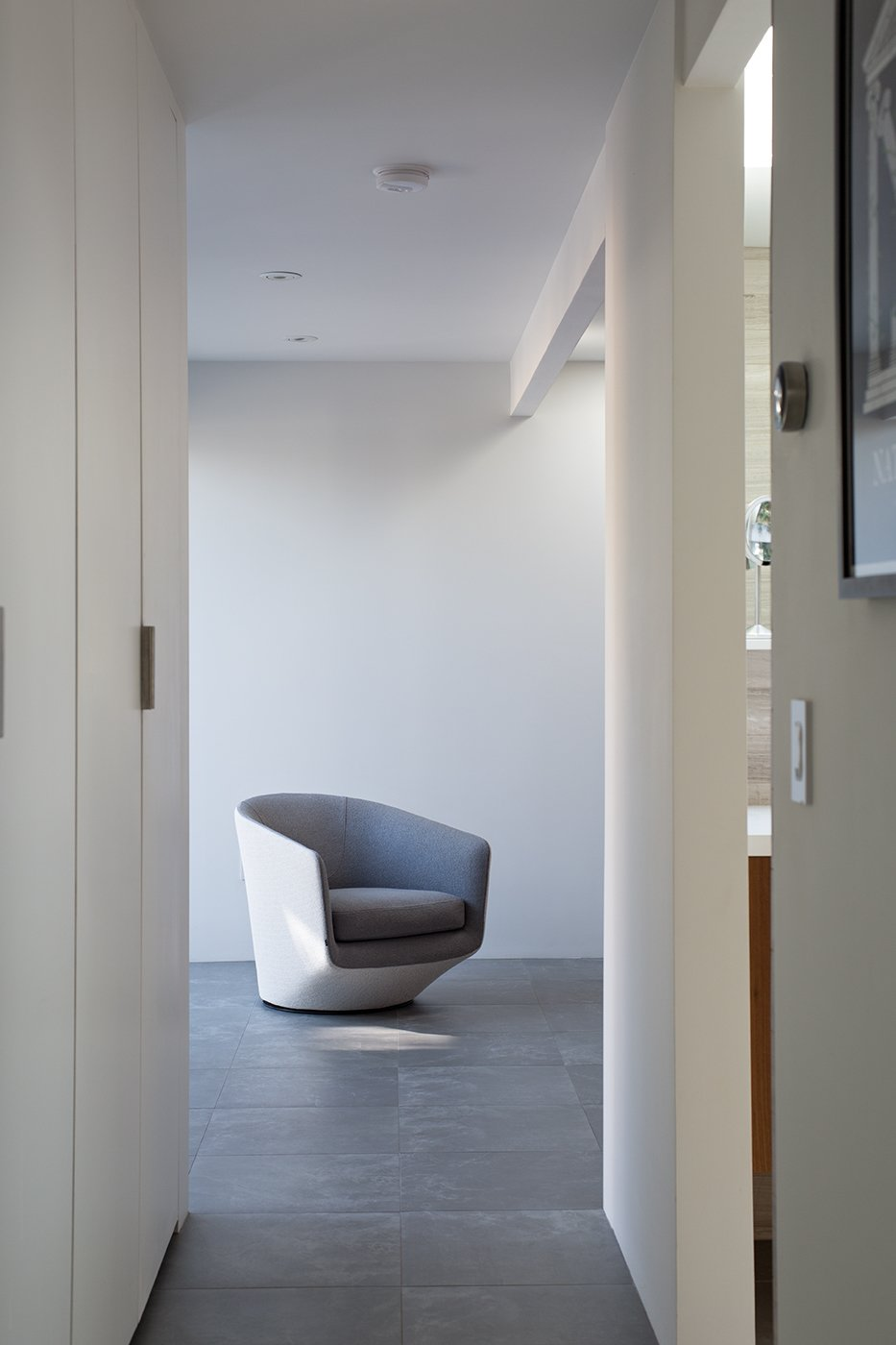 The floors are covered in two-foot square Nextra Piombo tiles by Monocibec. A U-Turn chair designed by Niels Bendtsen echoes the crisp, sculptural qualities of the interior spaces. Tagged: Hallway and Porcelain Tile Floor.  100+ Best Modern Seating Designs by Dwell from Indoor-Outdoor Home by a Midcentury Master Gets a Faithful Update