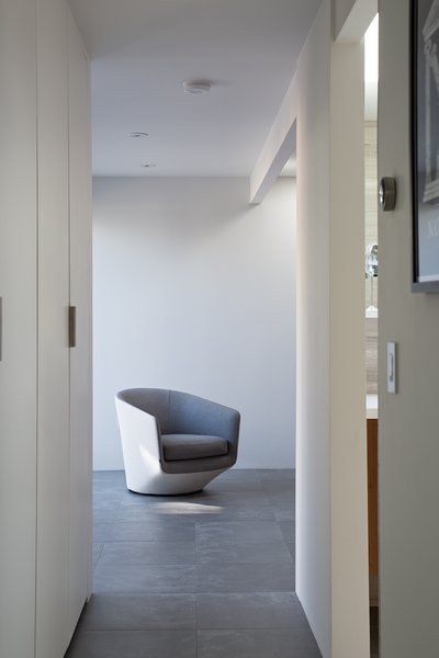 The floors are covered in two-foot square Nextra Piombo tiles by Monocibec. A U-Turn chair designed by Niels Bendtsen echoes the crisp, sculptural qualities of the interior spaces.