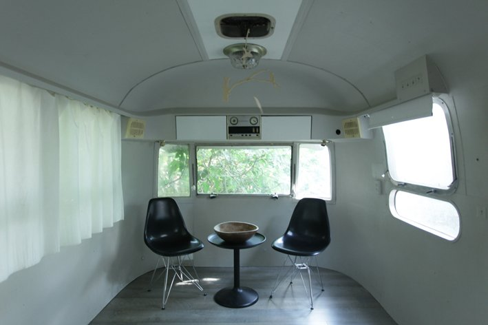 The egg-like living room doubles as the children's bedroom after dark, thanks to mattresses stored in a custom banquette in the studio area. The sole decorative elements are Eames shell chairs, an Ikea table, and a balsa-like children's mobile received as a gift.  8 Ways to Renovate an Airstream by Erika Heet from An Airstream and Playroom by the Beach