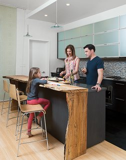 Sustainability Guided Every Decision at this Town House Remodel in Harlem - Photo 1 of 12 - David Alan Basche, Alysia Reiner, and their six-year-old daughter, Liv, chat in the kitchen, which is defined by a reclaimed spalted maple countertop crafted from a felled 100-year-old specimen sourced by The Hudson Company. The barstools are from Blu Dot.