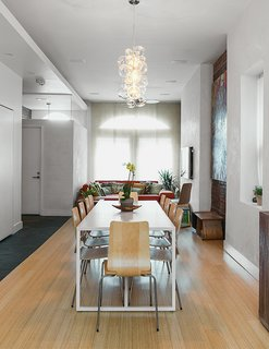 Sustainability Guided Every Decision at this Town House Remodel in Harlem - Photo 2 of 12 - The design team enclosed the vestibule of the front entrance to offer an area in which everyone can remove shoes and coats. The dining area boasts a handmade pendant by The Light Factory in Baltimore, Maryland. The table is from Blu Dot; the chairs are from Ikea. The flooring is natural bamboo from Dyerich.