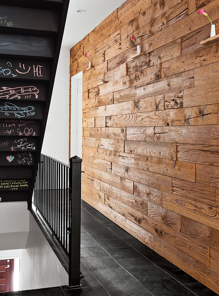"""On the second-floor landing, just outside Liv's bedroom, is the family's """"mushroom wall,"""" comprised of a blend of cypress and hemlock repurposed from the bedding bins of a mushroom-growing facility. During the mushroom growth cycle, enzymes digest and erode the soft wood grain, producing an organic, sculpted effect. ECOS chalkboard paint—zero VOC and non-toxic, natch—appears under the stairs. Tagged: Hallway.  Photo 4 of 12 in Sustainability Guided Every Decision at this Town House Remodel in Harlem"""
