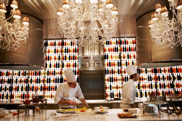 "A pair of chefs prepare dishes in the open kitchen at Raffles' one Michelin-starred restaurant, La Cuisine,  described as ""refined, generous, and spontaneous French cuisine."""