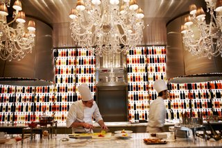 """Raffles Paris: A True Art Hotel - Photo 10 of 10 - A pair of chefs prepare dishes in the open kitchen at Raffles' one Michelin-starred restaurant, La Cuisine,  described as """"refined, generous, and spontaneous French cuisine."""""""