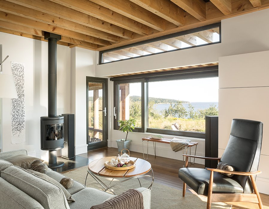 The living room is furnished with a Tolomeo Mega floor lamp by Artemide, a Milo Baughman Recliner 74, a Morsø 7648 wood stove, and a Hampton rug by Capel Rugs. Tagged: Living Room, Sofa, and Chair.  Photo 7 of 7 in An Artist Builds a Wooden Home That Lets Nature Be the Boss