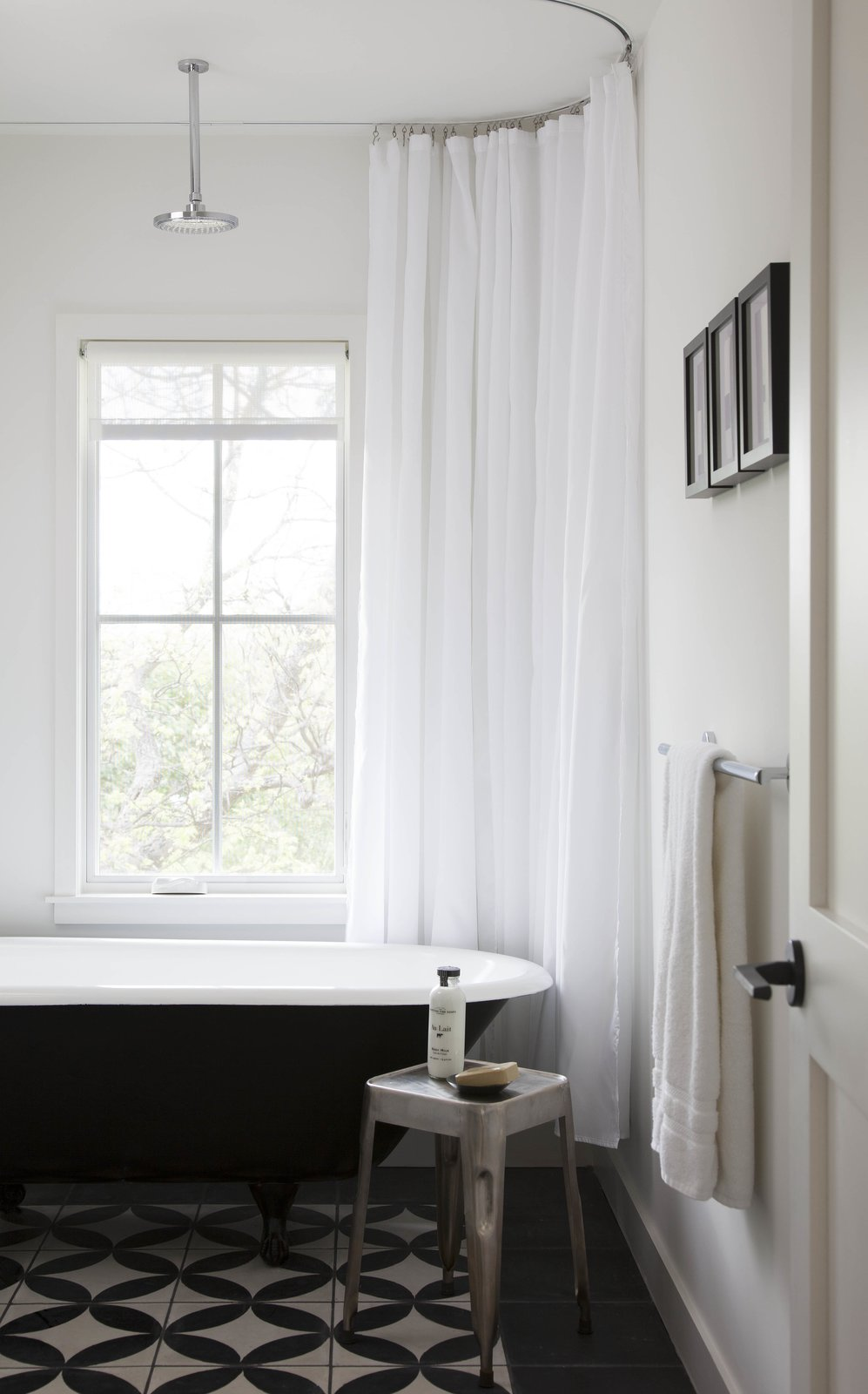 The juxtaposition of black and white is perhaps the most notable detail of the home's interiors. In the guest bathroom, black and white tiles provide visual interest. Tagged: Bath Room and Freestanding Tub.  Photo 4 of 8 in Modern Take on a Texas Farmhouse