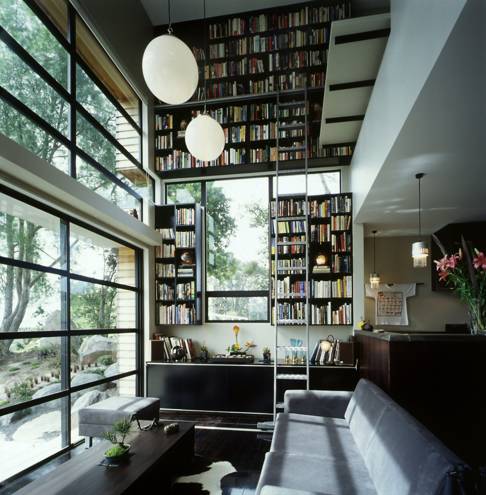 Hughes' collection of hundreds of books is stored on a vertiginous two story bookcase, which takes up the whole of the northern wall of the living room. It's an ingenious solution to the small-space dwelling that draws the eye up, adding texture and interest to the room without taking up floor space.