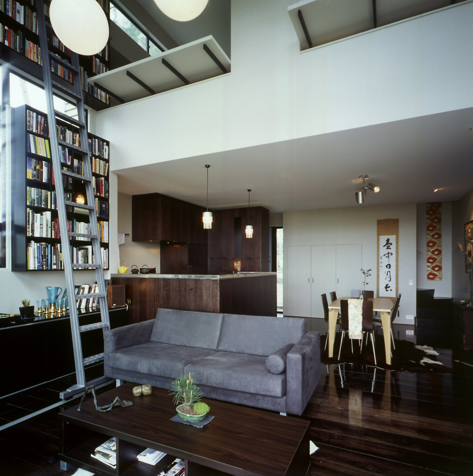The central area uses the available space in a deceptively simple way. With the kitchen to the left and bedroom to the right, two offices are stacked above it and accessed by a stairway in the rear of the room. Family antiques and Japanese textiles composed of complementary textures turn what is essentially a boxy space into a welcoming home. This Japanese-Style Box Home Boasts a Two-Story Bookcase - Photo 2 of 7