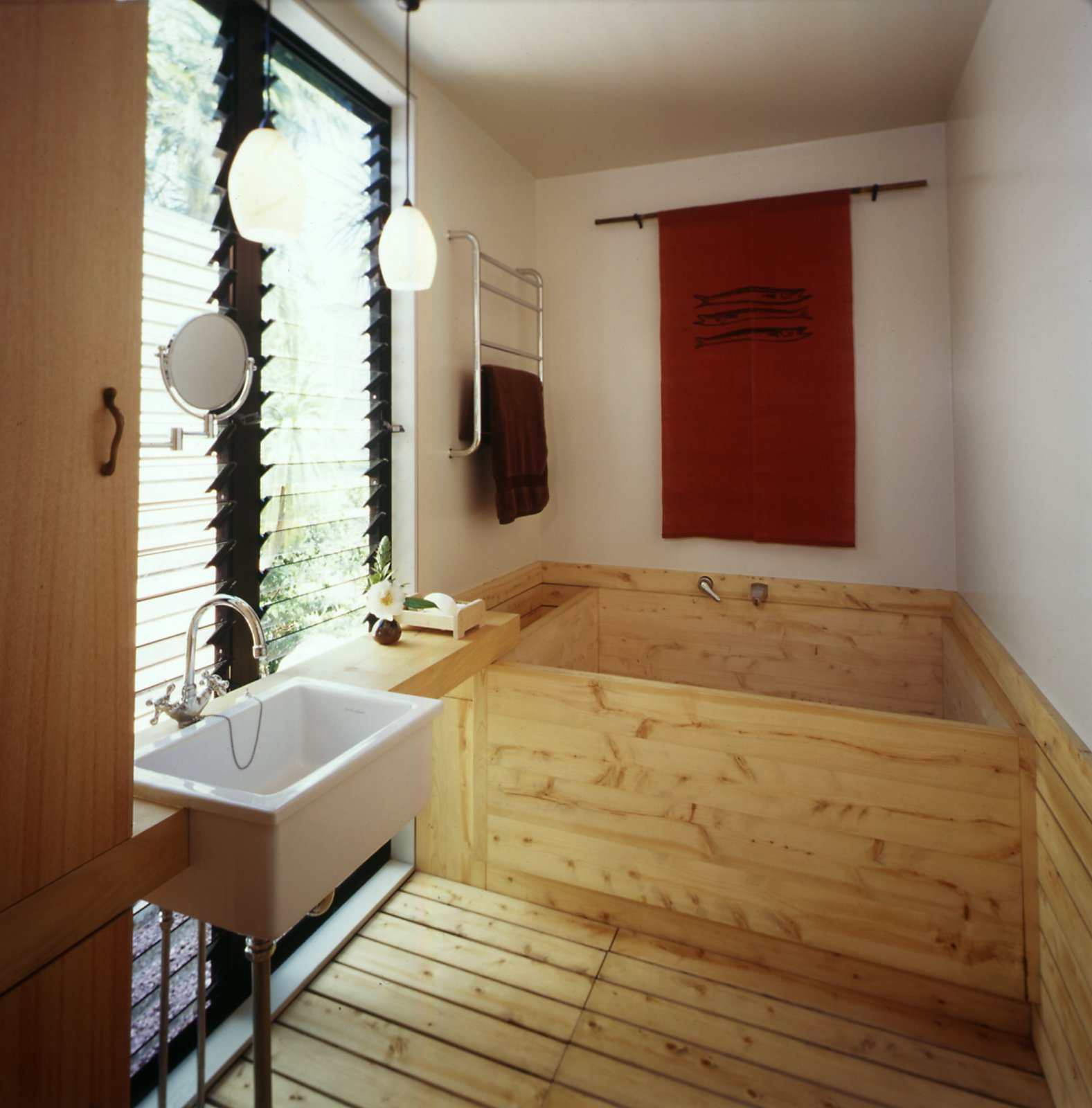 The traditional Japanese bathroom is located just off the central passageway between the two parts of the house. The couple wash here before bathing and relax in the wood-lined onsen, or tub.  Photo 4 of 7 in This Japanese-Style Box Home Boasts a Two-Story Bookcase