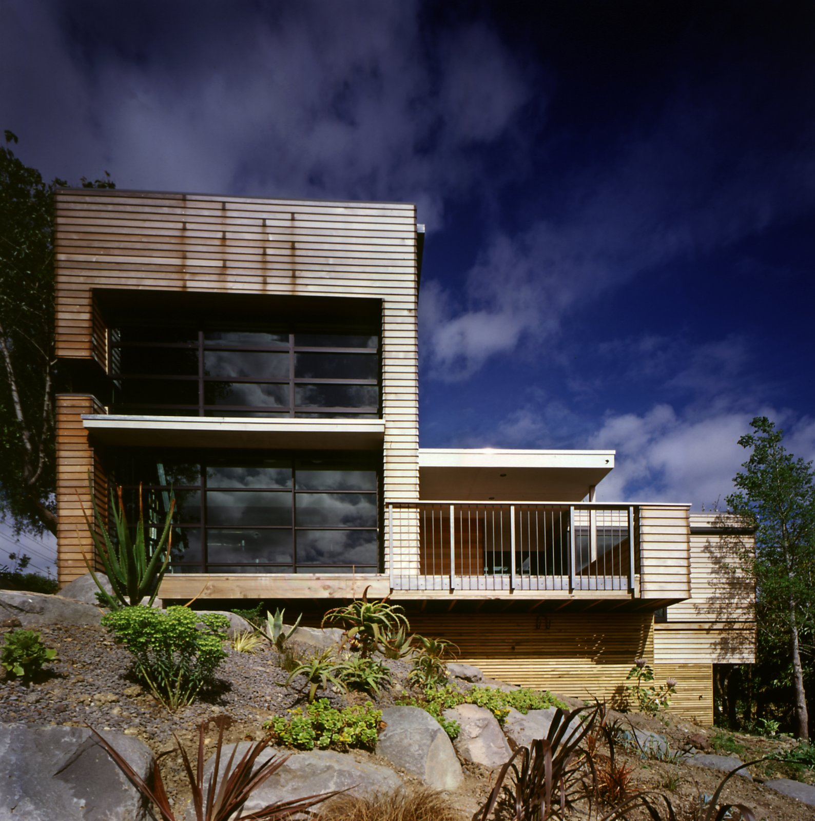 """The home's Canadian cedar cladding and aluminium joinery is low-maintenance, and designed to weather gently over time. The natural finish blends well with the surrounding garden, with its sculptural, desert plants. """"We face south-west, so the weather comes straight at us, and the wind is loaded with salt,"""" says Hughes. """"Fortunately, the plants we liked don't give a hoot about the wind."""" 20 Desert Homes - Photo 23 of 23"""