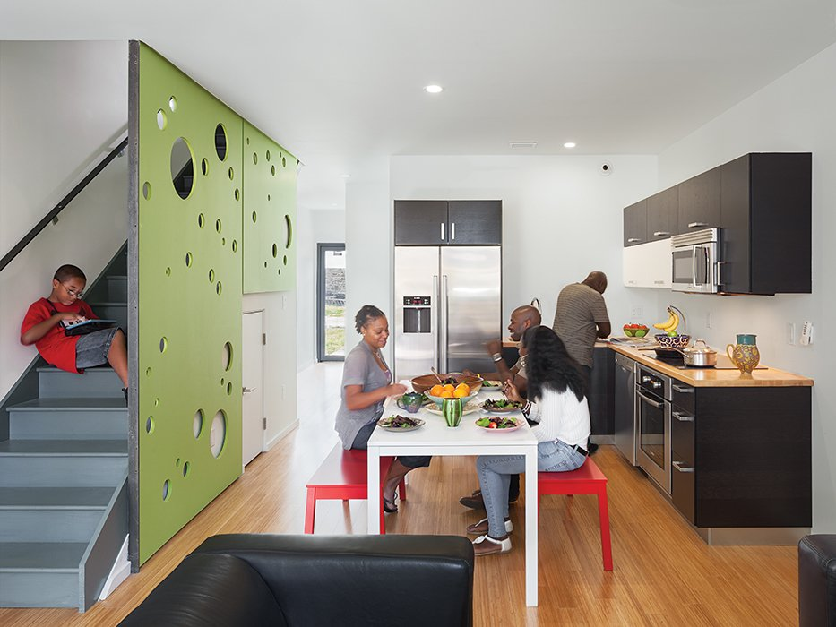 Each of the Belfield Avenue residences is outfitted with carbonized bamboo floors and Bosch appliances, including an induction cooktop. Onion Flats designed the medium-density fiberboard screen, whose round perforations serve as a filter for sunlight and a playful surface for children.