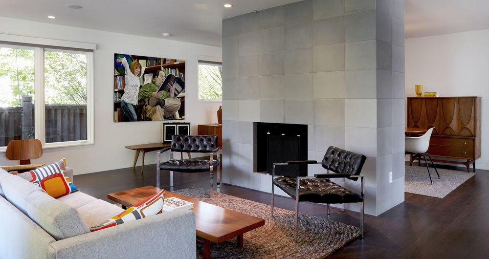 The new living room is open and bright. A hearth sheathed in concrete tile from Sadlerstone—a material that recurrs throughout the interior—is the space's focal point. Much of the vintage furniture came from Retro Inferno.  Raconteur Renovations: Homes with Some Serious History by Matthew Keeshin from Renovating a Modern House in a Historic District
