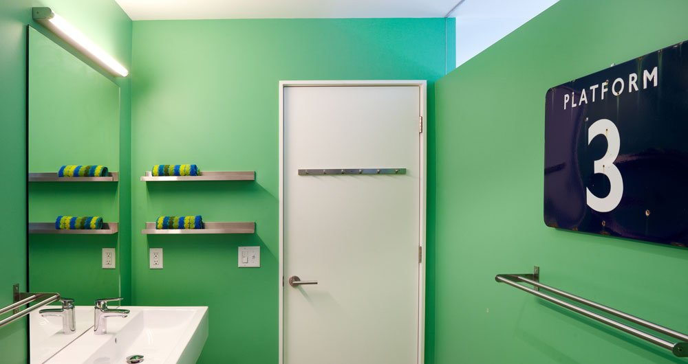 Bright paint in the bathroom offsets the white living room. A transom brings natural light into the space. The faucets are Grohe Europlus.