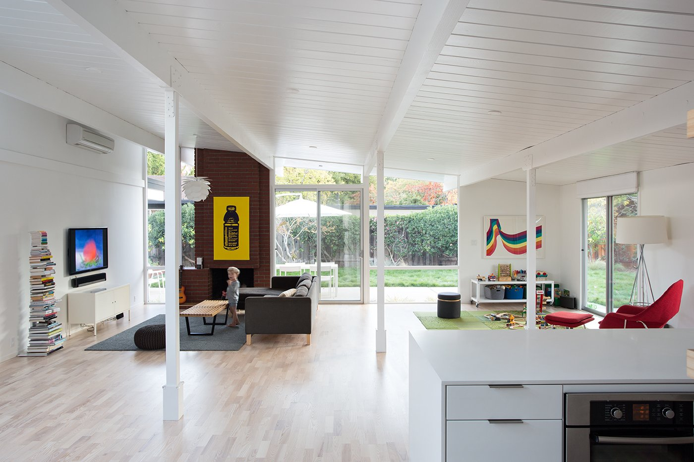"The living spaces of house, built in 1972 or 1973, were originally divided into three—a kitchen, living and dining area, and an atrium (previous owners had covered the atrium with a roof). ""The new owners wanted the interior space to flow as one, so we removed the glass doors and solid walls separating the enclosed atrium from the kitchen and living room,"" principal John Klopf says. ""Some structural posts needed to remain to hold up the roof, but overall the space was opened up almost completely. The floor was leveled, and the plan freed up."" The rainbow print is a 1960s Herman Miller trade poster, and the Vitamin Water print by a New York artist. A Sapien book tower from Design Within Reach sits next to the TV. The sofa is IKEA."
