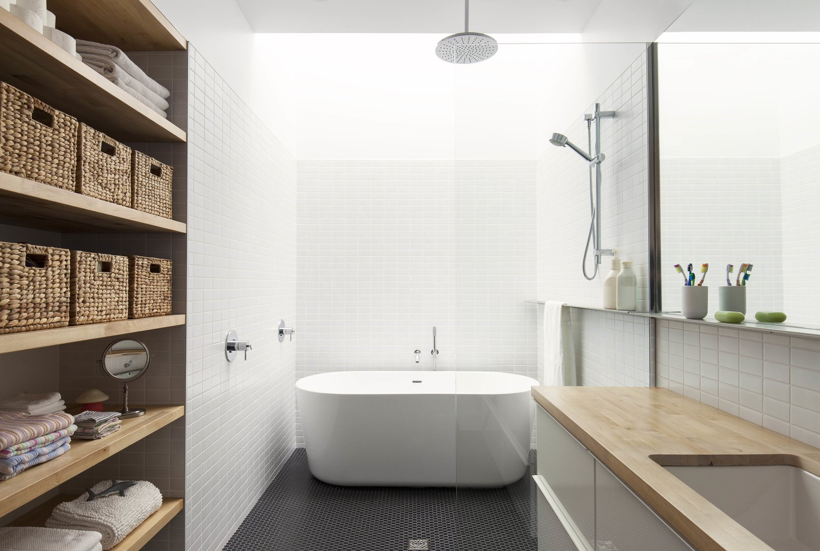 In the renovated bathroom, a freestanding bathtub sits beneath a skylight that runs the width of the room. A large mirror hangs above the vanity, which is outfitted with a butcher-block countertop. Black mosaic tiles were used on the floor.