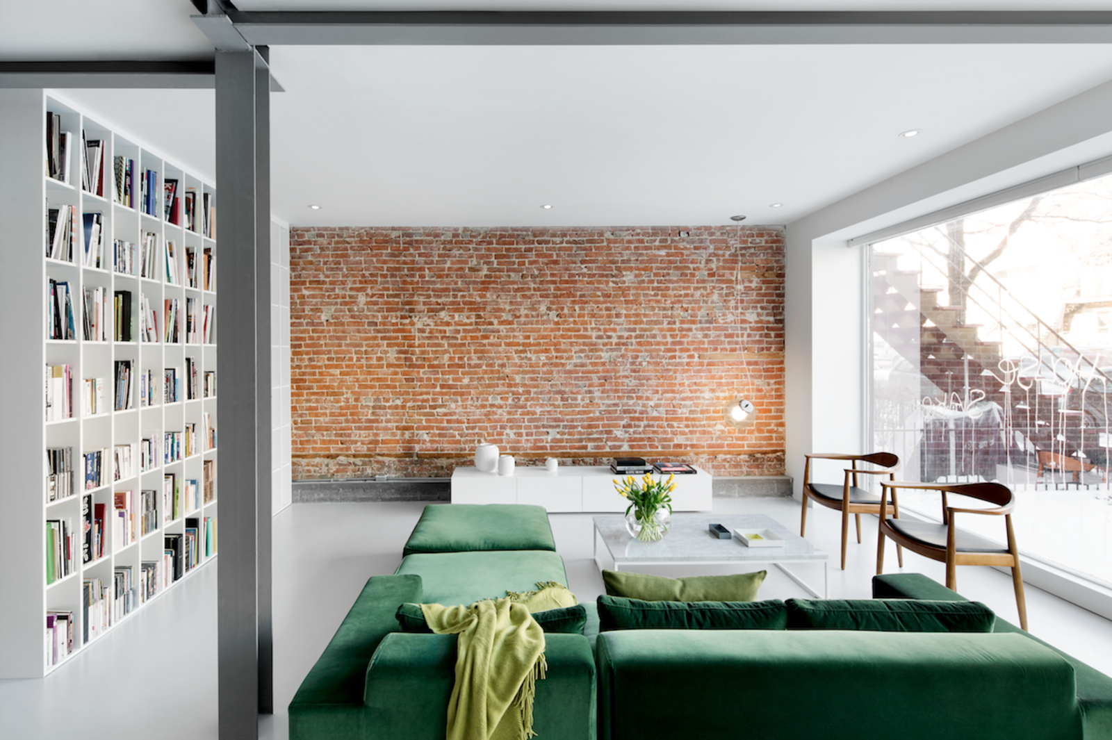 Goneau highlighted the red brick wall in the living room by leaving it bare and protecting it behind museum-quality glass. The space also features a floor-to-ceiling window that's coated on the outside with a reflective film, letting residents keep their curtains open by day without fear of being seen from the street. The green sofa is by St-Laurent Domison and the white oak chairs are by Hans Wegner. All other furniture is custom. Tagged: Living Room, Coffee Tables, Pendant Lighting, Bookcase, Chair, Console Tables, Sectional, and Concrete Floor.  Best Photos from A Futuristic Apartment with a Glass-Enclosed Bedroom