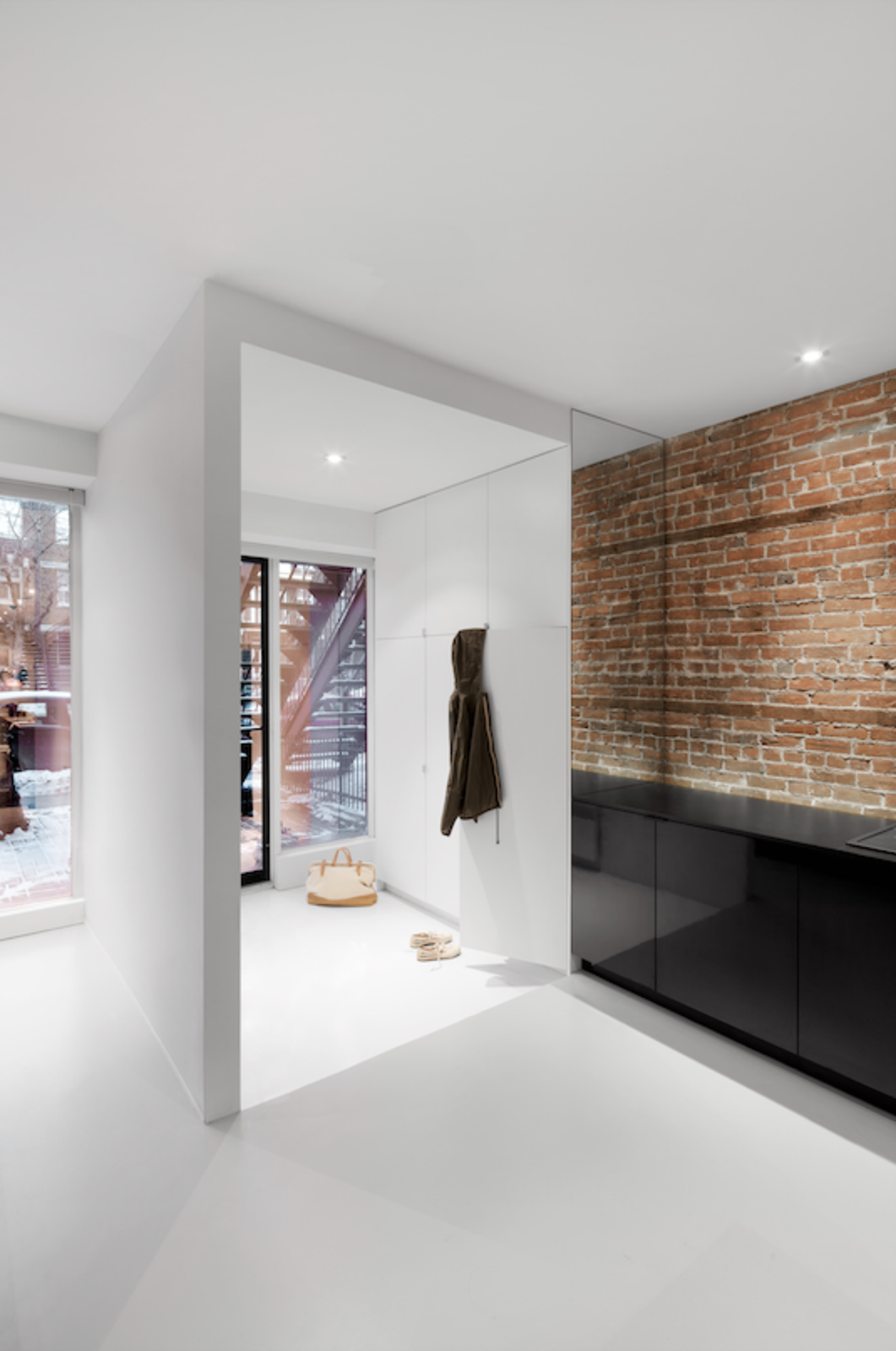 The semi-closed entryway contains a white cabinet for storing coats and scarves. The LED ceiling lights are from Contrast Lighting. Tagged: Hallway.  Photo 4 of 11 in 10 Fantastically Sleek Foyer Designs from A Futuristic Apartment with a Glass-Enclosed Bedroom