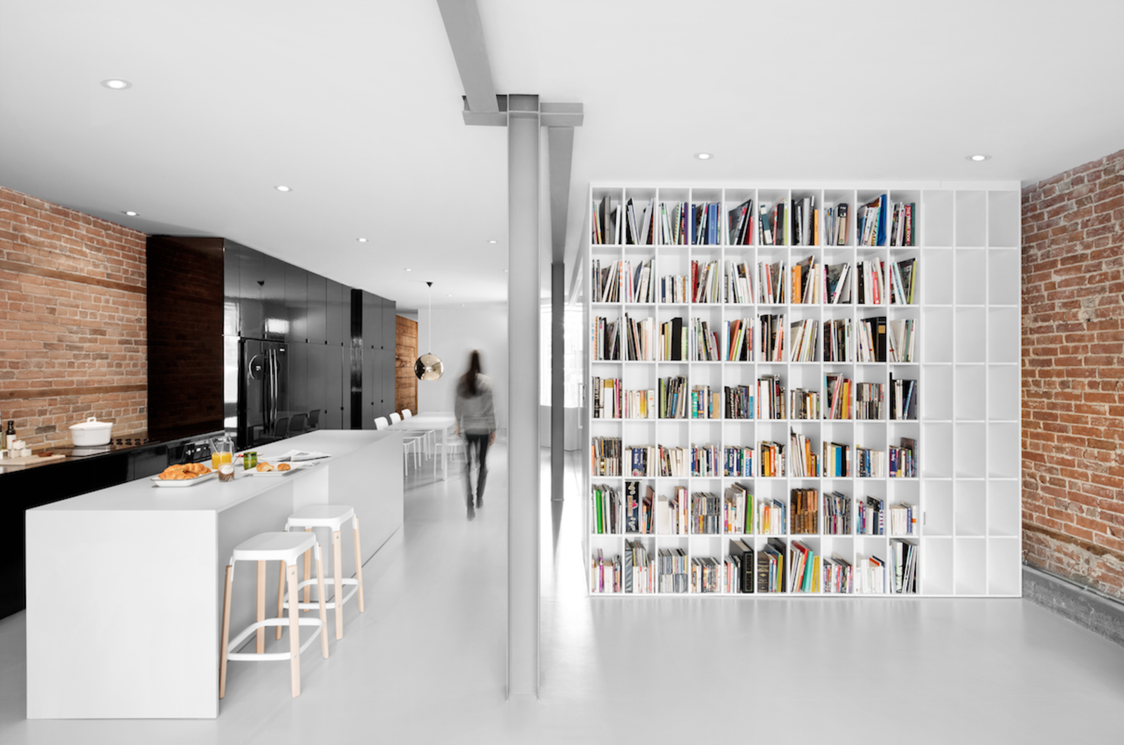 The steel beam original to the building was left exposed but toned down with gray, flame-proof paint. It runs the length of the flat, delimiting the passage area. Tagged: Kitchen and White Cabinet.  Storage by Dwell from A Futuristic Apartment with a Glass-Enclosed Bedroom