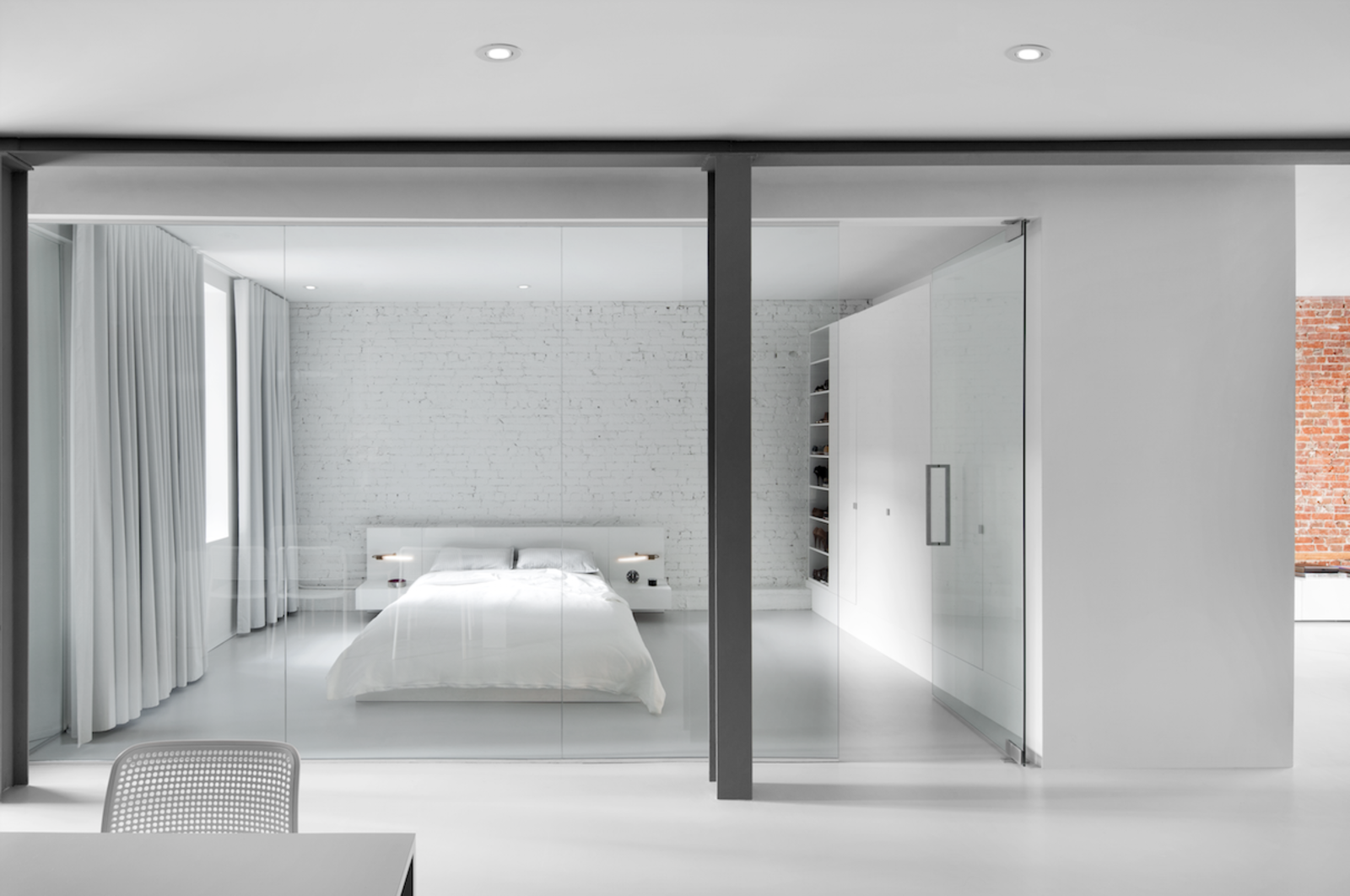 The bedroom is enclosed with a glass wall. A blackout curtain can be drawn closed for privacy. An Ikea cabinet and custom white lacquered shelves provide plenty of closet space. Tagged: Bedroom and Bed.  Best Photos from A Futuristic Apartment with a Glass-Enclosed Bedroom