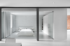 Modern home with Bedroom and Bed. The bedroom is enclosed with a glass wall. A blackout curtain can be drawn closed for privacy. An Ikea cabinet and custom white lacquered shelves provide plenty of closet space. Photo  of Unusual Sleeping Spaces