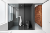 Modern home with Bath Room. A original hemlock wood wall clads the corridor leading to the bathroom. Just inside, the dark gray epoxied shower area (with a Cimarron Kohler toilet) forms a solid contrast to the white walls and floors. Photo  of A Futuristic Apartment with a Glass-Enclosed Bedroom