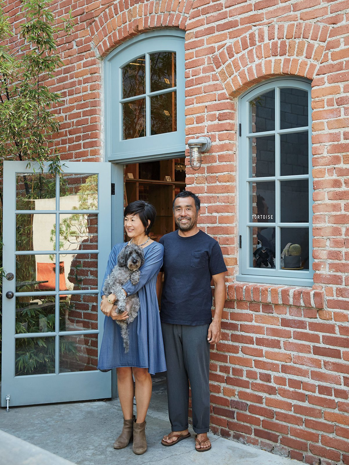 Keiko and Taku Shinomoto (with Fido—pronounced FEE-do) stand outside Tortoise, which is set off by a small outdoor courtyard.  Photo 6 of 6 in A Cute Mom-and-Pop Shop in L.A. Showcases the Latest Japanese Design