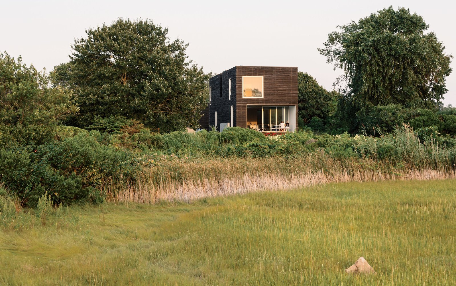 Native New Yorkers, the Merola family have long held a tradition of spending summers in Rhode Island. When they learned the costs of renovating their existing cottage would significantly outweigh the benefits, they instead opted to build new. The result—a distinctively modernist box structure clad in milled slats of charred, brushed, and oiled cypress manufactured by Delta Millworks—sits nestled within the marshy landscape of Quonochontaug Pond. Add a Home to Dwell - Photo 1 of 3