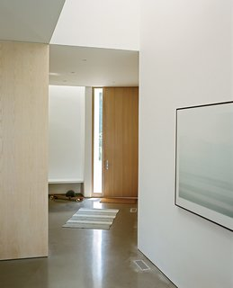 A custom entry door by Creekside Millwork is positioned diagonally from the home's rectilinear form.