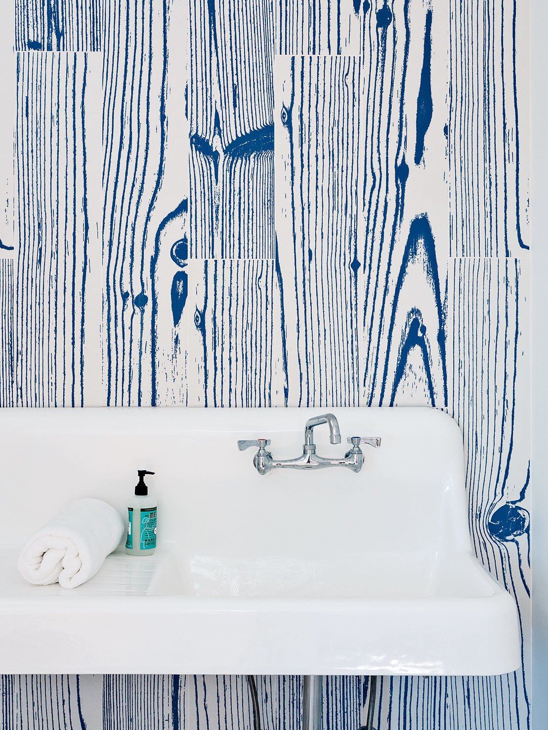 White-and-blue, wood-grain–patterned UonUon tiles by 14oraitaliana line the bathroom walls in a loft above the garage. Tagged: Bath Room and Wall Mount Sink.  Photo 9 of 20 in 20 Bathrooms With Transformative Tiles from An Idyllic Rhode Island Summer Cottage Is the Perfect Escape for a New York Family