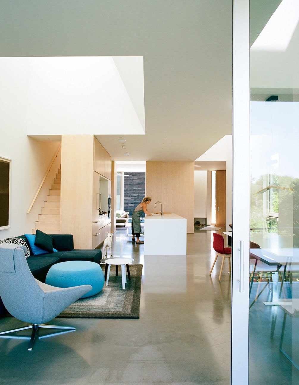 The kitchen contains an island countertop made of Corian in Glacier White. Tagged: Living Room, Sofa, Chair, Ottomans, Coffee Tables, and Concrete Floor.  Photo 8 of 16 in An Idyllic Rhode Island Summer Cottage Is the Perfect Escape for a New York Family
