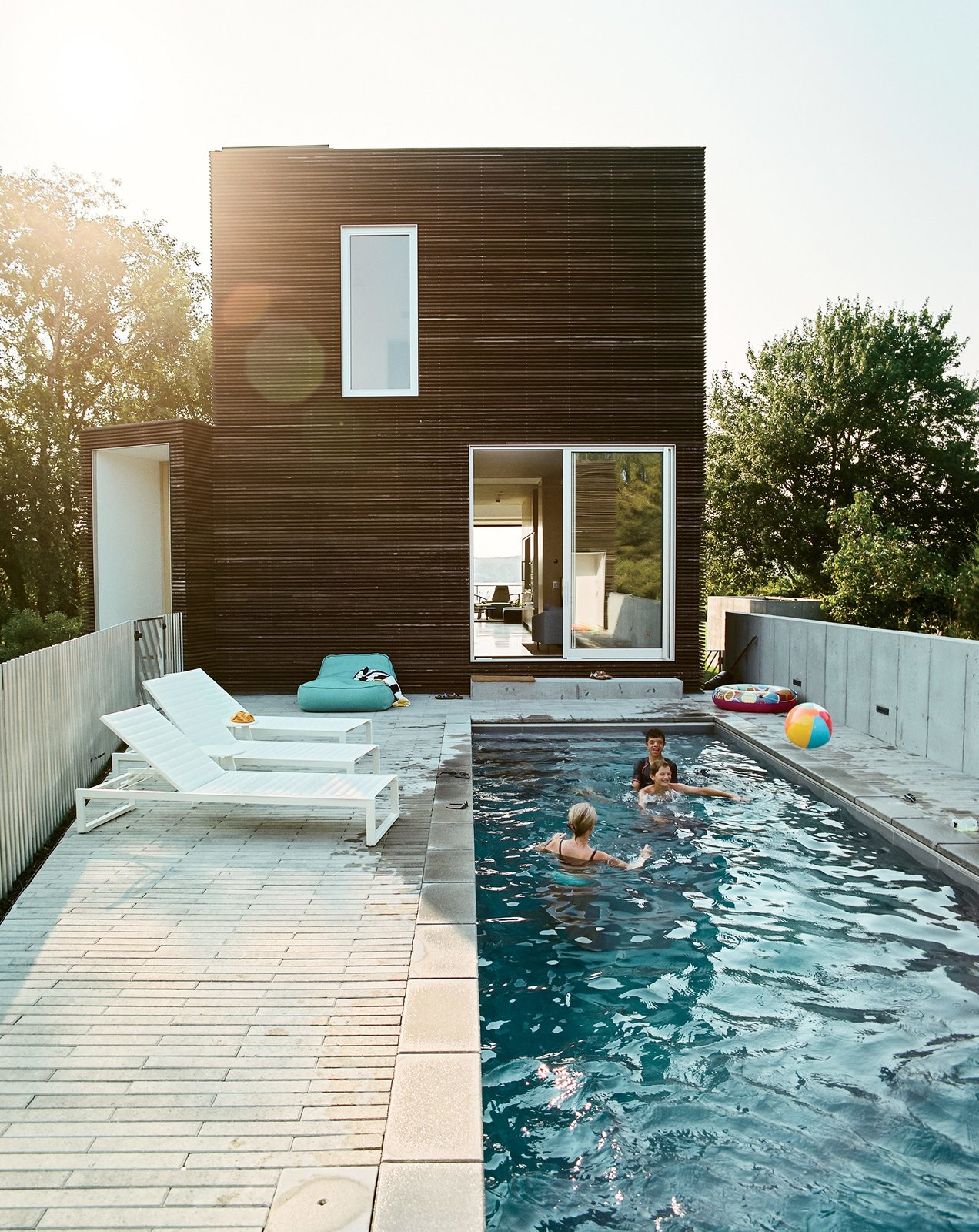 The east-facing pool terrace is outfitted with a series of Eos lounge chairs (and plenty of inflatable swim toys). Tagged: Concrete Patio, Porch, Deck, Swimming Pools, Tubs, Shower, Small Pools, Tubs, Shower, Lap Pools, Tubs, Shower, Back Yard, Exterior, House, and Wood Siding Material.  Modern Pool Design by Dwell from An Idyllic Rhode Island Summer Cottage Is the Perfect Escape for a New York Family