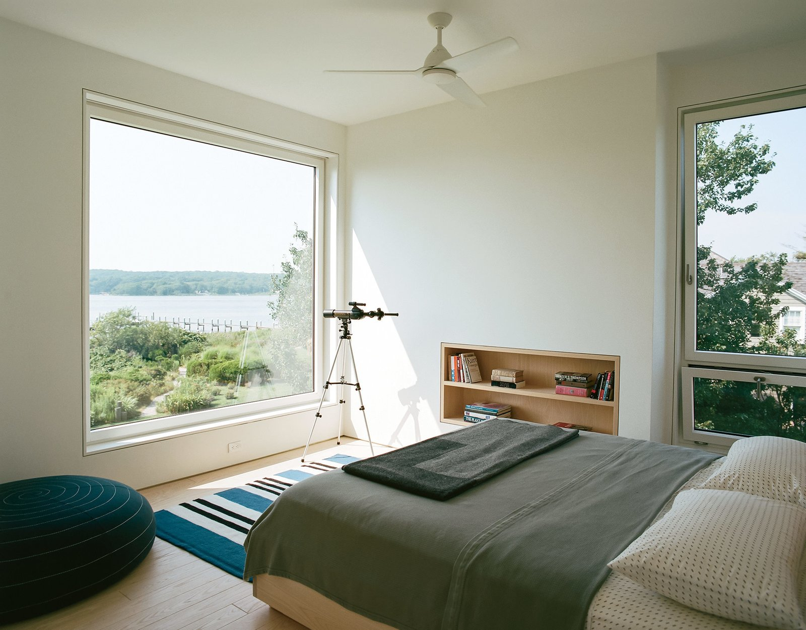 In the master bedroom, a custom ash frame takes advantage of the expansive view. Tagged: Bedroom, Bed, and Shelves.  Photo 16 of 16 in An Idyllic Rhode Island Summer Cottage Is the Perfect Escape for a New York Family