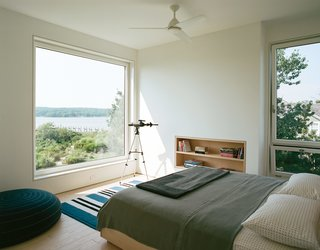 In the master bedroom, a custom ash frame takes advantage of the expansive view.