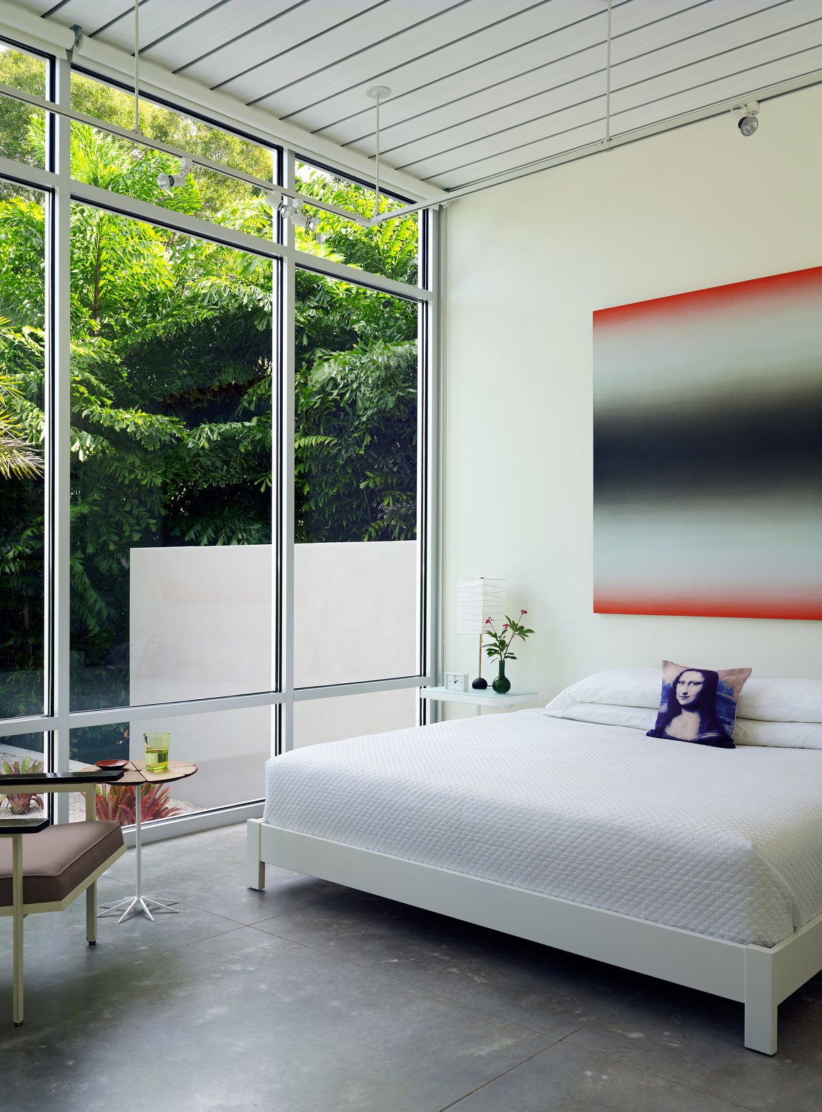 In the master suite, a painting by Eric Freeman hangs over a West Elm bed. Tagged: Bedroom, Bed, Chair, Night Stands, Track Lighting, and Concrete Floor.  Bedrooms by Dwell from This Sparkling New Home Is a Perfect Remake of Classic Sarasota School Modernism