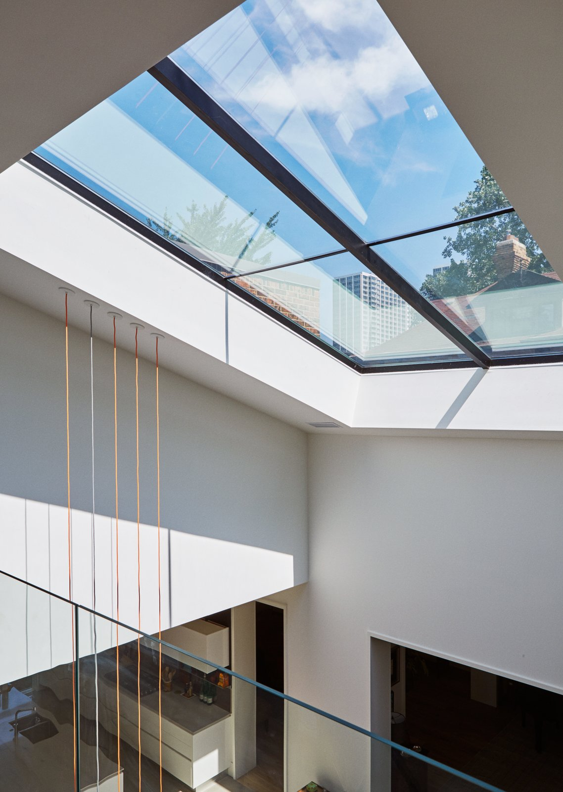 A newly expanded window over the atrium allows glimpses of the surrounding neighborhood. An Impressive 20-Foot Skylight Transforms a Jumbled Chicago Home - Photo 11 of 13