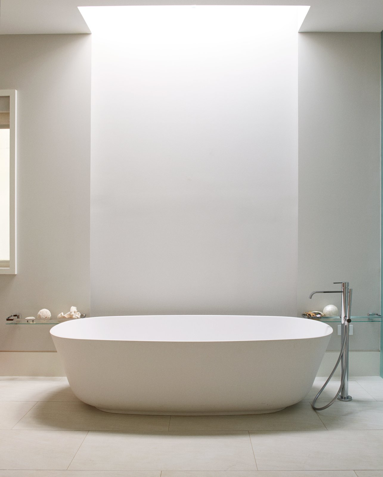 A freestanding Antonio Lupi tub defines the updated master bath, which also features an open-plan layout and a skylight by Velux. An Impressive 20-Foot Skylight Transforms a Jumbled Chicago Home - Photo 13 of 13